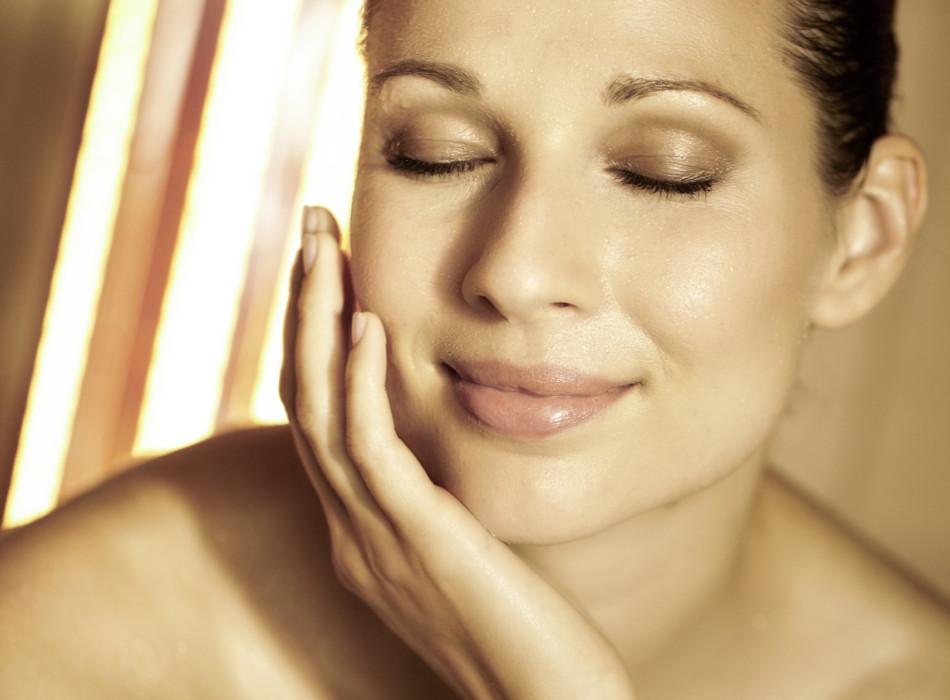 Frau in der Sauna die ihre Augen zu hat und entspannt lächelt