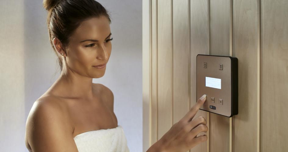 Frau mit Badetuch die Einstellungen an der Sauna vornimmt